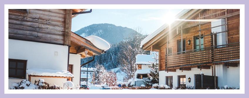 Verschneite Häuser In Den Bergen An Einem Sonnigen Tag. Titelbild Für Den Blogbeitrag: Tipps Zur Planung Einer Ferienimmobilie Mit Einem Architekten