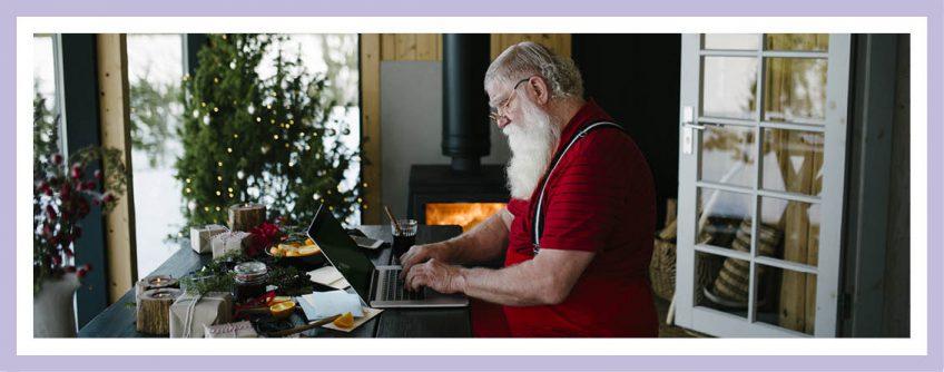 Frohe Weihnachten! Ein Bloggender Weihnachtsmann Sitzt In Seinem Wohnzimmer. Ein Schwedenofen Wärmt Ihn Und Im Hintergrund Steht Ein Weihnachtsbaum!